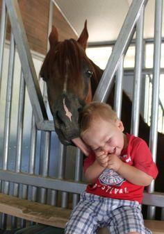 A horse tickling a little boy with his tongue. sooo cute