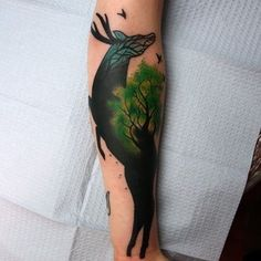 Really cool, abstract deer and tree tattoo with birds flying around the top on the arm. I really like the aesthetic of the deer's face.   No Artist Information