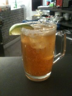 michelada cocktail is a beer cocktail in beer mug garnished with salt and lime wedge on glass rim