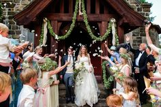 Wedding guests throwing petals at the bride and the groom as they exit this beautiful stone church.
