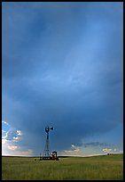 Windmill and tractor under a threatening stormy sky. North Dakota, USA