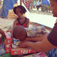 When this little one opened his shoebox he found a photo of a young boy. As it was explained to him that this was the boy who had packed the box for him, he bent over and kissed the photo. #Zambia