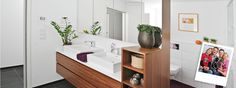 Upgrade baths to wood with stone counters and above counter sinks. Open shelves above toilets handy for guests and cheaper.  Easy to dust/clean. Modern lines.