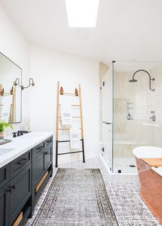 Well appointed bathroom features a gray and blue rug placed on gray quatrefoil floor tiles in front of a dark gray dual washstand complemented with oil rubbed bronze hardware matching oil rubbed bronze faucet fixed to a white quartz countertop beneath a black framed mirror.