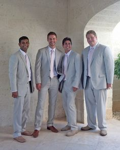 Groomsmen attending a destination wedding in Turks and Caicos looked airy yet elegant in light-colored suits and pink ties.