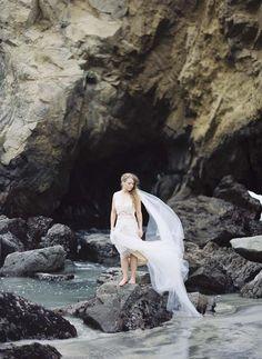 Rocky beach, flowing veil. Seaside Lovers destination wedding: Romantic, Whimsical, Natural.