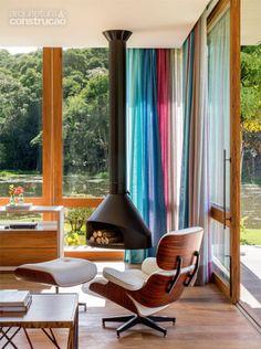 Painéis de vidro temperado de 10 mm (2,15 x 3,10 m cada um), encaixados em esquadrias de peroba (Madeireira Vale), cercam grande parte do estar. A lareira de ferro suspensa é da Construflama. Projeto de Skylab Arquitetos.