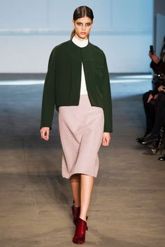 Derek Lam, New York Fashion Week Fall 2014. Serene clean look with nude oversized skirt, white high collar shirt, dark green oversized collarless jacket, burgundy ankle boots.