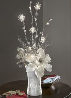 Centerpiece Ideas    A dramatic silvery, glittery holiday centerpiece at over 2-ft. high, this poinsettia will dazzle far beyond Christmas. Set in a faux mother-of-pearl vase, the ivory fabric poinsettia with glitter center stands out among glitter-covered leaves and tall, bendable wire branches accented with clear beads and 12 glowing LED flowers. On/off switch. Uses 3 AA batteries (not included).     Lighted Ivory Poinsettia Bouquet from Seventh Avenue ®