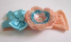 Faixa infantil de meia de seda com uma flor de cetim em tom pêssego e azul e um laço de fita de cetim azul.