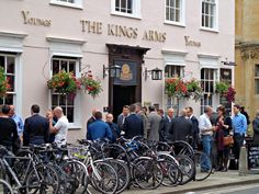 A bustling pub, The Kings Arms, at the city center of Oxford. By looking at it, this place seems the nexus of the social universe. Men of different dress gather outside, pint in hand, in a buzz of chatter. It appears as if the bikes are joining them - in this instance, the pub and the street are mingled together as one. In great places and incidents such as these, it is fantastic to examine and appreciate the active and various role of the pub in this community as a tradition that holds true…