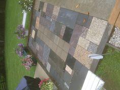 Granite rectangular pieces around cement squares on top of stone dust.