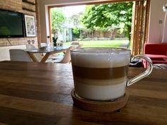 Morning cafe latte on walnut kitchen counter top overlooking oak bi-fold doors into garden