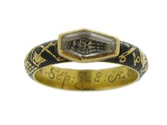 Georgian enamelled memorial ring set with rock crystal. Horizontally set to centre with a faceted coffin shape rock crystal in a stepped rubover setting on to an intricate depiction of a skeleton, flanked by a smooth conforming band with black enamel and an etched raised relief of an extremely intricate yellow gold full reclining skeleton with skull and cross bones, flowing around the band.