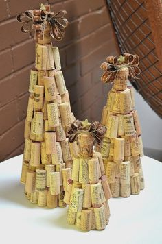 A set of 3 rustic cork Christmas trees decorated with hand-cut repurposed wine corks and topped with a champagne cork with ribbon and gold star.