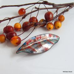 Part of my Flora Designs, inspired by foliage, my shaped brooch was formed from hand cut and shaped copper and finished with glass enamel. Many layers of fine glass are bonded to the metal, front and back, under high heat in a kiln. This leaf pin is one of a kind. It is a piece of art jewelry inspired by nature. It features patterns and areas of opaque and transparent enamels. Its bright, durable, and fun to wear.  Pin measures about 2 3/4 (69 mm) long and about 1 (23 mm) wide at the widest…