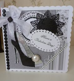 I stamped a shoe out three times & then cut pieces off to make the shoe 3D. Cut some shapes out off my spellbinders & added some crush ribbon & bling. the stamp is a Chloe stamp.