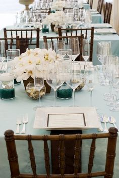 A magnificent guest table for a wedding and reception at a private estate in Southern California. Centerpieces of phalaenopsis orchids make the perfect elegant beach chic wedding.