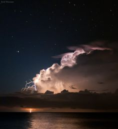 Bolts of lightning illuminate an offshore thunderstorm beneath stars of the constellation Bootes.