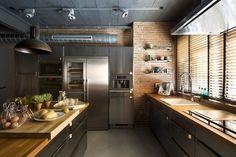 cuisine style industriel avec un mur de brique exposée, des armoires en bois et des plans de travail en bois massif