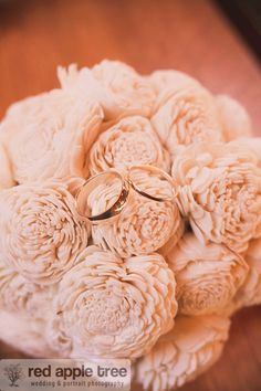the wedding rings on the bride's paper flower bouquet