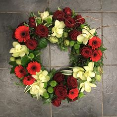 A stunning, modern funeral wreath featuring grouped red and green flowers including roses, gerbera and orchids with textured foliage and a twisted willow twig accent. #Vegetablegardenideas