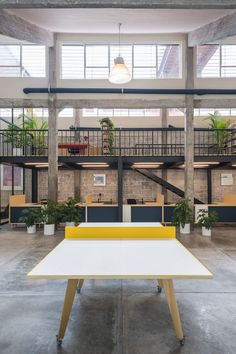 Mexican architects Estudio Atemporal has paired concrete columns and cinder-block walls with black metal and glass partitions when transforming a former industrial factory in Mexico City into a co-working space.