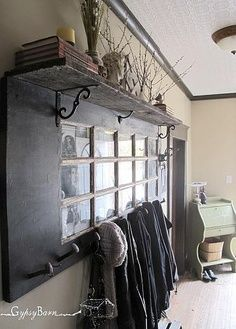 Flea market find-old french door repurposed in an entryway for coats and hats<3 - I like this idea - could also use the window panes as dry erase for notes, calendar reminders, etc.