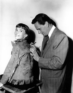 "Natalie Wood, 11, turns her back to Wendell Corey so he can add his name to the autographs she is collecting on her leather suede jacket in Hollywood, Calif., on Nov. 15, 1949. They both appearedin ""No Sad Songs For Me."""