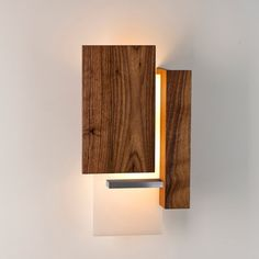 The Vesper LED Wall Sconce is a simple, geometric sculpture composed of brushed aluminum, oiled black American walnut, and white polymer.