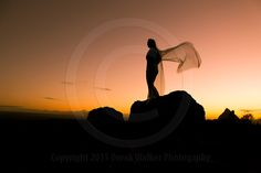silhouetted woman standing on the peak of Mt. Ngungun at sundown in the Glasshouse Mountains, in Queensland, Australia.  For image licensing enquiries, please feel welcome to contact me at derekwalker73@bigpond.com  Cheers :)