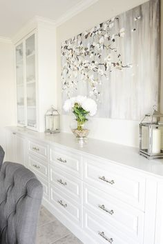 Beautiful dining room with built-in sideboard accented with polished nickel hardware and a simple ...