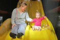 Samen met mama glijden van de glijbaan in Heggies Speelschuur.
