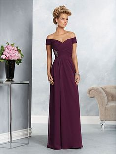 A long formal gown with an off-the-shoulder neckline, natural waist with a medallion, and draped A-line skirt.