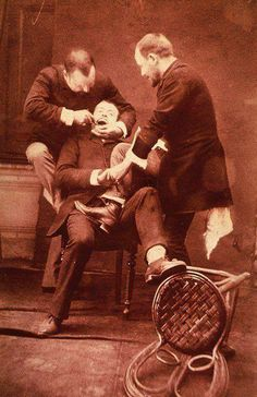 a dentist pulling a tooth out? dentist, patient, assistent, history, photograph, vintage, photo, sapira