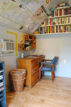 Garden shed interior - love the posters on the ceiling and the book shelf right up in the corner!