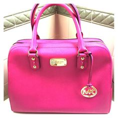 """Michael Kors pink dome satchel Michael Kors Satchel Saffiano Leather with leather trim Gold tone hardware Dimensions: 10"""" wide (at base) 8.5"""" wide (at top) x 7.5"""" tall x 5"""" deep - size SMALL Handles - drop 3.5"""" Removable & adjustable strap - drop 19"""" - 23"""" Zip closure MK signature lining with interior cell sleeve, sleeve pockets & zip pocket. Hanging MK logo circle charm Feet on base. Used 2-3 times. Great condition. Michael Kors Bags Satchels"""