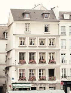 Creamy white house with pink flowers and curtains hanging in the windows - European city architecture