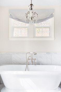 Alyssa Rosenheck - Sara Ray Interior Design - Elegant bathroom features a small crystal chandelier placed above a roll top bathtub and a vintage tub filler.