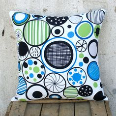 The moving circles represent infinity, free movement and change. Graphic drawings in orange-red or colder hues of cyan are symbolically placed inside them. Match it with a classic black pillow for contrast or a white one to make the drawings pop.