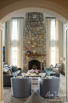 """Double height (plus?) ceilings can be a challenge! Great use of drapery, fireplace finish, and wall treatments to keep the space feeling """"human-sized"""" 