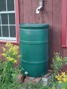 Dark Green Rain Barrel Elevated On Bricks Top Helps Keep Leaves Out
