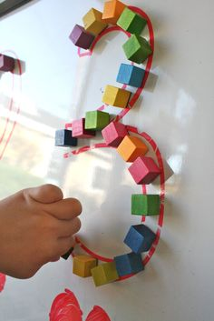 "Lay items over large written numbers to have a sensory experience of what they look like ("",)"