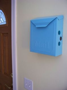 Standard metal mailbox from the hardware store, primed and spray painted aqua and used to hide mail clutter.