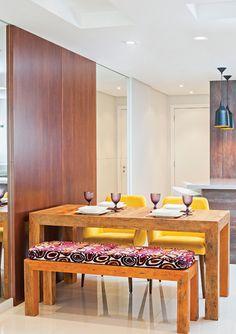 No espaço de jantar, o toque rústico vem com a madeira de demolição especificada na mesa e no banco, cujo assento traz uma composição descontraída. (pode-se colocar o banco embaixo da mesa, ganhando espaço)