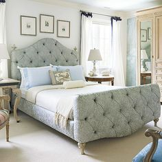 Oversize furniture emphasizes the large scale of this spacious bedroom. The large tufted bed frame, upholstered in a beautiful brocade fabric, is placed between the room's two windows and steals the show as the main focal point. A massive armoire along one wall provides plenty of storage space and keeps the room looking balanced.