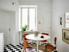 HEM&RUM.se | Kitchen with white walls and black and white checkered floor. What looks like Saarinen table from Knoll, T-chairs 3103 by Arne Jacobsen for Fritz Hansen.