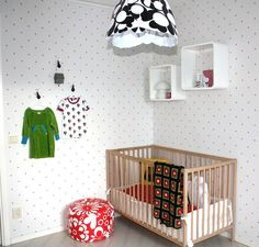 Colourful kids room with polka dot wallpaper.