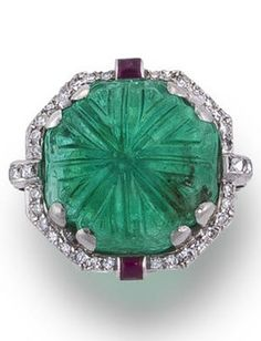 An Art Deco emerald, diamond and ruby ring, circa 1930. Centring an octagonal-shaped carved emerald framed by single-cut diamonds, with French-cut diamond three-stone shoulders and accentuated by two buff-top rubies; mounted in platinum. #ArtDeco #ring
