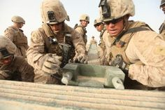 Marines move the nosepiece of a bridge into place in Mirmandab, Afghanistan, March 25. The Marines are part of Alpha Company, 9th Engineer Support Battalion, I Marine Logistics Group (Forward), and worked in support of Special Operations Task Force West.